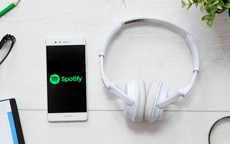 Spotify smartphone on desk with headphones