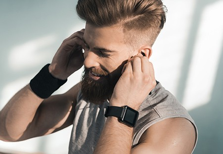 man listening to music on a smartwatch