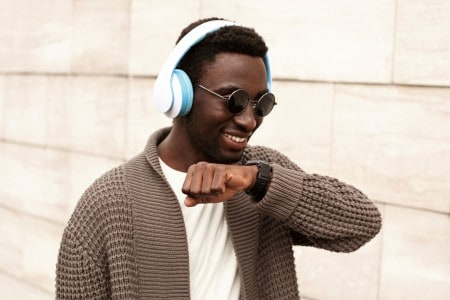 Portrait smiling african man with smartwatch using voice command recorder or takes calling in wireless headphones listening to music on city street over brick wall background