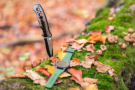 Hunting watch and knife on log