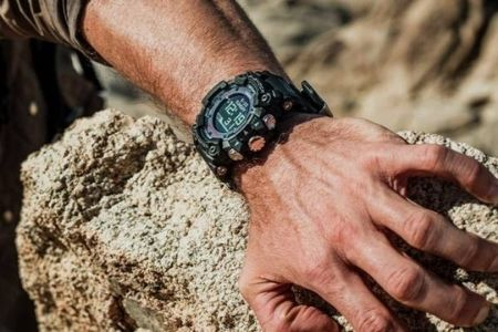 man with watch holding on the rock