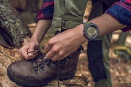 man with watch fixing shoelace