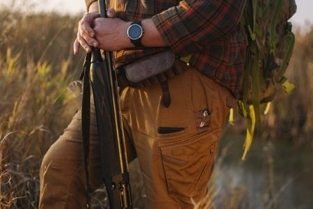 man with hunting weapon wearing watch
